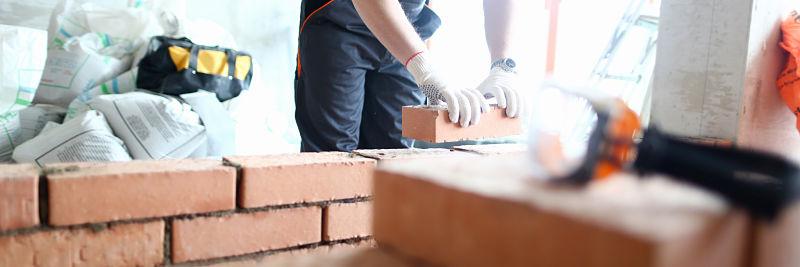 Ouvrier du batiment en train de monter un mur de briques rouges